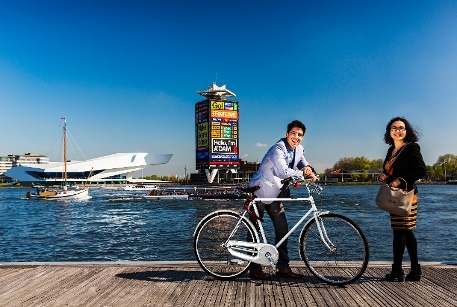 Amsterdam, man with bicycle, woman, on the river IJ