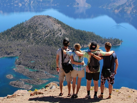 Four exchange students on a mountain admire  the view, a small island, while arm in arm.